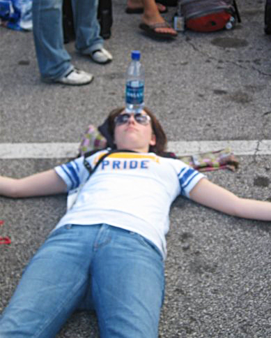 I wish I could say I staged this photo because it is too perfect for this topic- my shirt even says pride on it. This was in 2008 in Florida. When waiting for a bus I laid down in the parking lot with a water bottle on my head for my headache. I looked ridiculous, but I needed to do it.